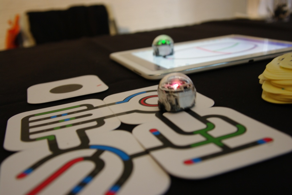 Ozobot following lines, colors and patterns on both paper and a tablet to help teach kids about robotics and programming.